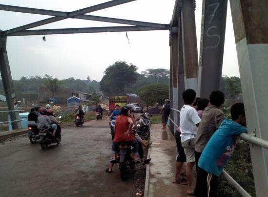Pengendara motor menonton dan mengabadikan banjir sungai Cikarang dari atas jembatan Cibening